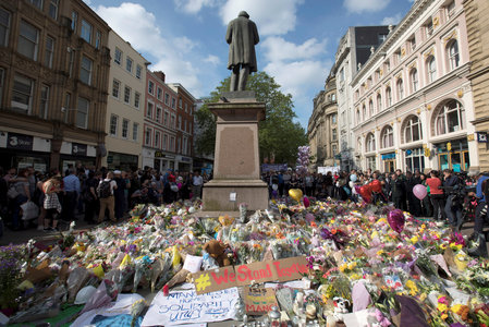 Messages and floral tributes left for the victims of the attack on Manchester Arena lie around the statue in St Ann's Square in central Manchester